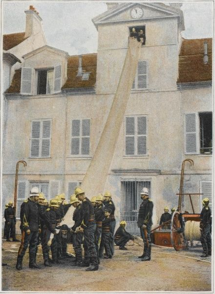 People trapped on upper floors escape from a blaze via a sac (chute) which they slide down head first to the sapeurs- pompiers waiting below