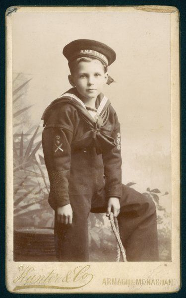 A little boy wearing a typical Edwardian sailor suit, with 'H.M.S. Trafalgar' on his hat