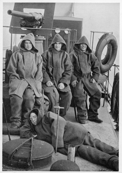 Four crew members on the deck of the torpedo boat destroyer 'Sturgeon', wrapped up against the elements in duffle coats