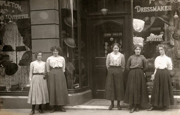 A group of well-presented young women - presumably sales assistants - stand in front of the windows of a dressmaker's and outfitter's shop