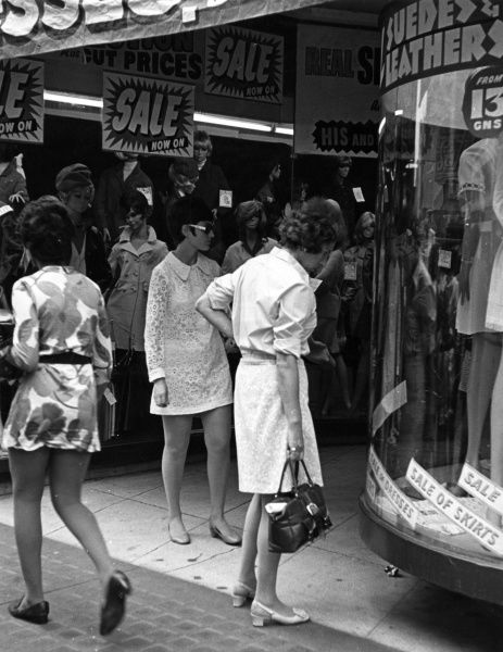 A middle aged woman looks in a shop window during the London Summer Sales. Is she wondering whether she can contend with the trendy dolly birds all around her? Date: late 1960s