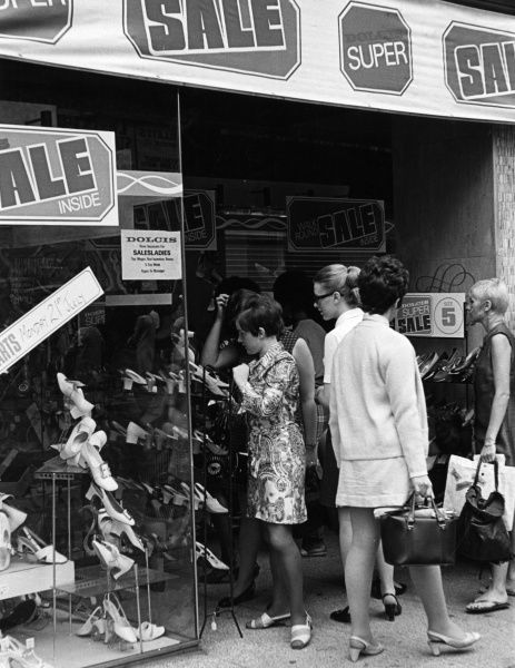 Young women hovering around a shoe shop during the Summer Sales, in the days when Paisley mini dresses were all the rage! Date: late 1960s