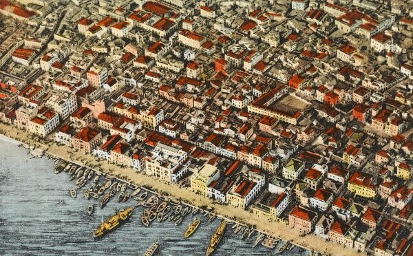 Birds-eye view of Salonica, showing the tightly-packed streets of the town centre (containing the Jewish Quarter) and houses and boats moored against the harbour. A terrible fire of August, 1917 decimated the centre of the town