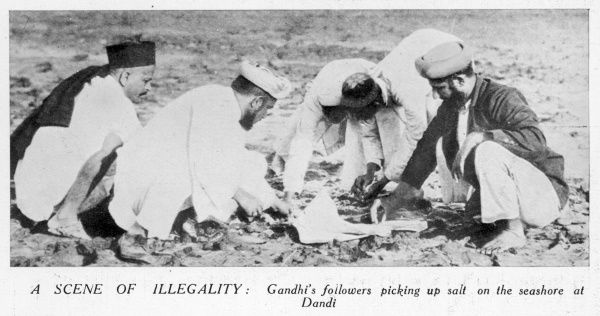 A scene of illegality : Gandhi's followers picking up salt on the seashore at Dandi at the culmination of the Salt March in India to protest against the British tax on salt