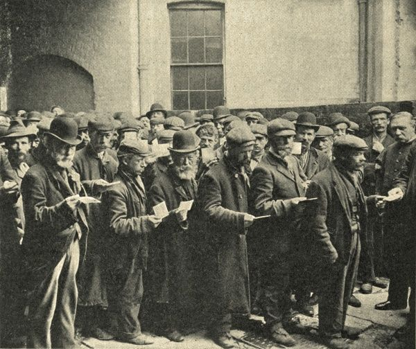 A crowd of vagrants waving tickets jostle for admission to the Salvation Army shelter (known as The Embankment) at 115B Blackfriars Road, London