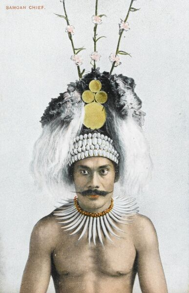 A superb postcard depiction of a Samoan chief with headdress decorated with shells, feathers and flowers and round gold plates and a fine handlebar moustache! He wears a necklace of Sperm Whale (cachalot) teeth