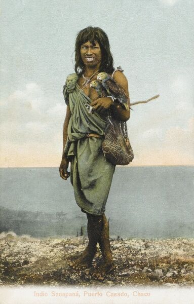 A Sanapana youth with string bag and holding two parakeets