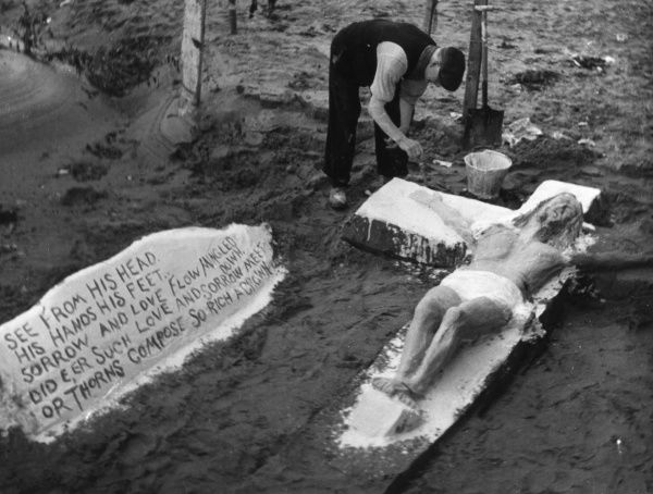A sand artist putting the finishing touches to a sand sculpture of Christ on the cross, Ayr beach, Ayrshire, Scotland. Date: 1930s