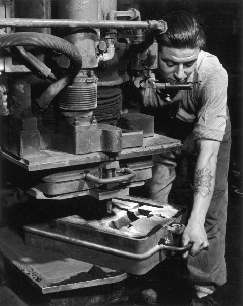 A factory worker slides a sand-filled mould into position beneath an industrial molten-metal dispensing machine. The man has a tattoo on his forearm which reads 'True = Love' and 'Mam = Dad'. Photograph by Heinz Zinram