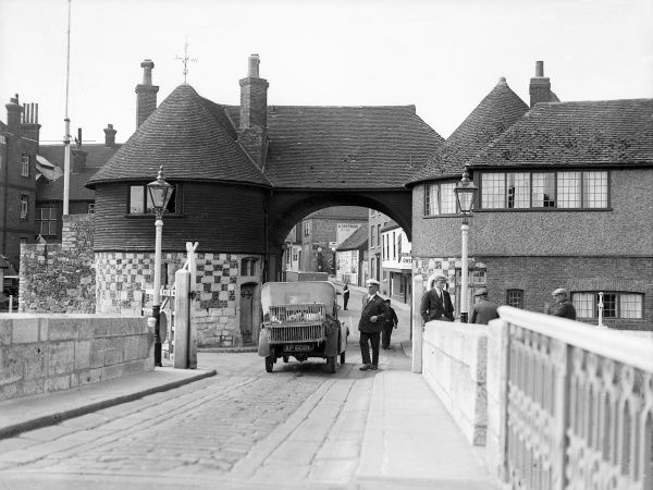 The Toll Bridge at Sandwich Kent, England and the smart gentleman in a peaked cap who used to police it. Date: 1930s