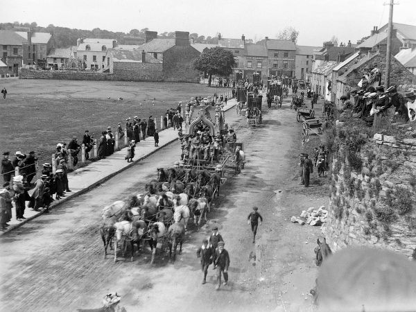 Street scene, showing part of Sanger's Circus parade during a visit to Haverfordwest, Pembrokeshire, Dyfed, South Wales, with several elaborate horse-drawn carriages, and riders dressed in fancy costumes. People on the pavements stop and look