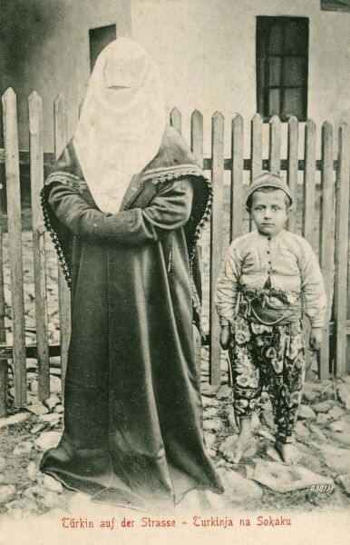 A Bosnian Turkish Muslim woman, her face completely covered by a white veil and her son, who wears some incredible floral trousers and a surprised gaze