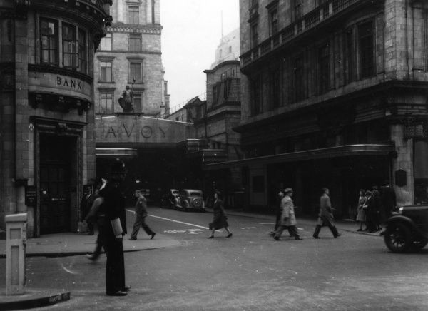 Entrance to the Savoy Theatre and hotel on the Strand, London with the National Provincial Bank on the corner. A policeman directs traffic. Date: 1947