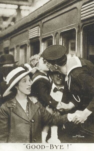 A departing British Royal Navy Sailor saying farewell to his wife and son as his troop train departs for port and then onward to battle in the First World War. Date: 1915