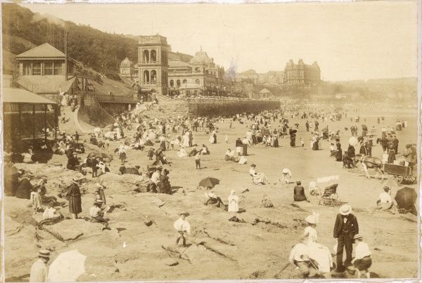Scarborough, North Yorkshire: a crowded summertime beach, with umbrellas used as parasols. The Spa building is in the centre, and the Grand Hotel in the right distance