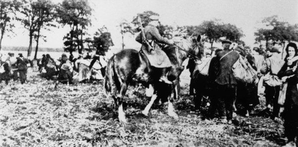 Mounted police drive off scavengers from the potato fields during the terrible shortages that followed the war