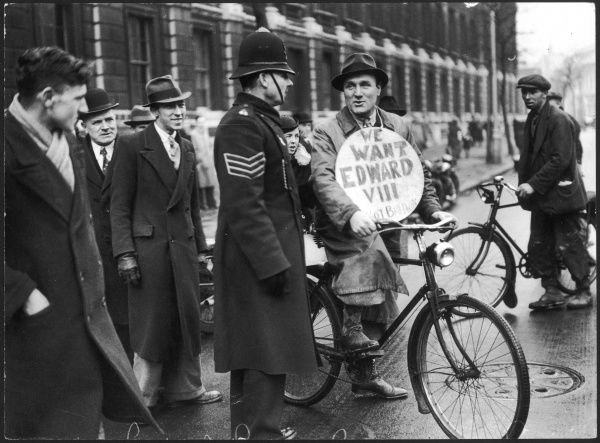 A cyclist sympathetic to the dilemma of King Edward VIII in December 1936, talks to a policeman in Downing Street, London. The king's desire to marry Mrs Wallis Simpson, an American divorcee split the government and resulted in a constitutional crisis