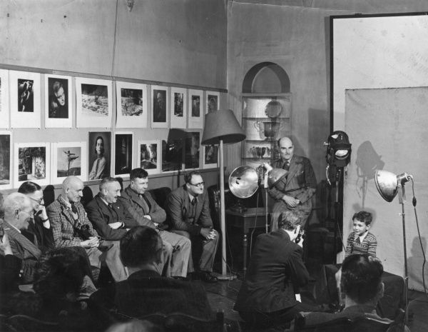 Scene in a photographer's studio. Several men, who appear to be photographers themselves, watch a photographer photographing a little boy, who seems to be enjoying the experience