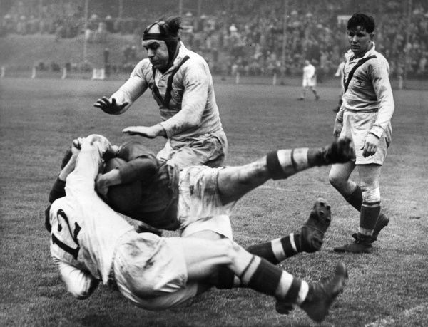 Scene at a rugby match, with two players colliding.  circa 1940s
