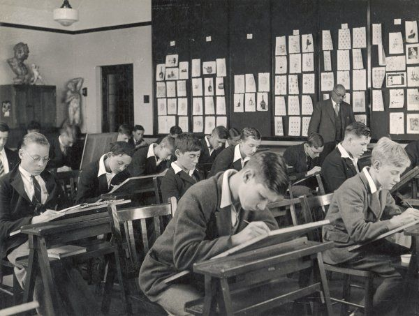 A serious looking class of boys at work during an art lesson, with some of their previous work pinned to the wall of the classroom