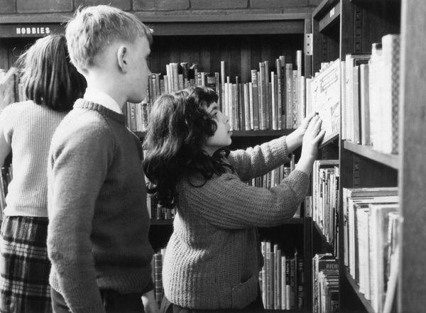 Pupils search for books on the shelves of the school library. Date: 1950s