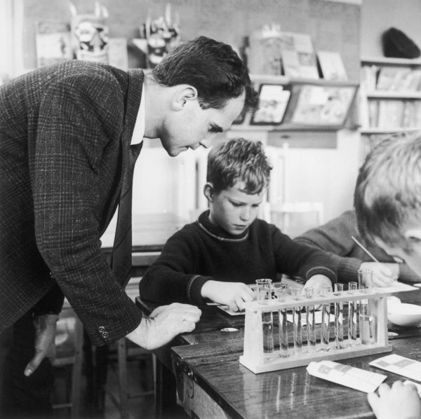 Teacher helps pupil with his test tube experiment at Northfield House Junior School, Leicester