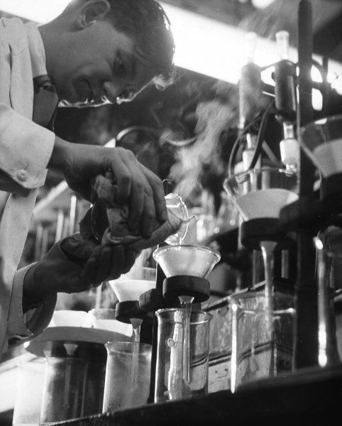 A scientist pours liquid into a beaker using a glass funnel. Date: 1955