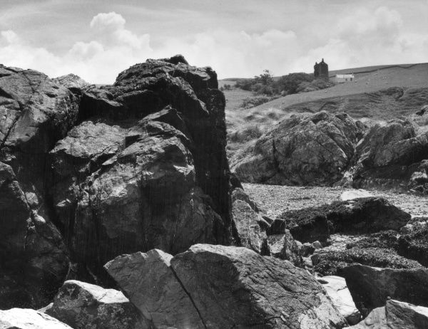 Cliffs by the shore at Lendalfoot, near Ballantrae, on the Ayrshire coast road, Scotland. Carleton Castle is in the background. Date: 1950s