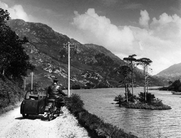 A motorcycle and sidecar on the 'Road to the Isles' along the northern shores of Loch Eilt, Scotland, with its tiny islets, beautifully canopied with tall pine trees. Date: 1950s