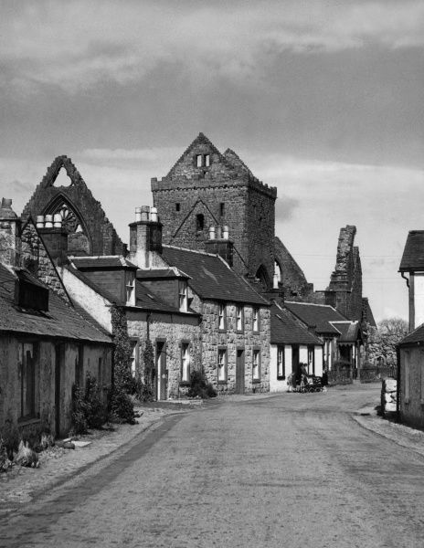 The quaint village of New Abbey, on the border of Kirkoudbrightshire, Scotland, overshadowed by the gaunt ruins of the 13th century Sweetheart Abbey. Date: 1950s