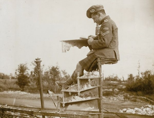 A resourceful Scottish soldier sits on a section of spiral staircase on the Western Front during the First World War to write his letter home. Date: 1914-1918