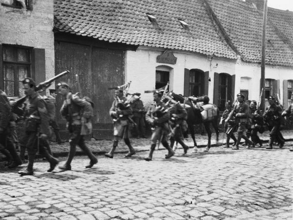 Scottish troops and pipers playing bagpipes marching through a French village on the Western Front in France during World War I in 1915