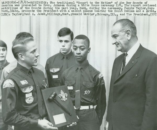 "Boy Scout Ferris Taylor presents President Johnson with a walnut plaque bearing the Scout emblem and a gavel. The traditional ""Report to the Nation"" of the Boy Scouts of America was presented to President Johnson during a White House ceremony"