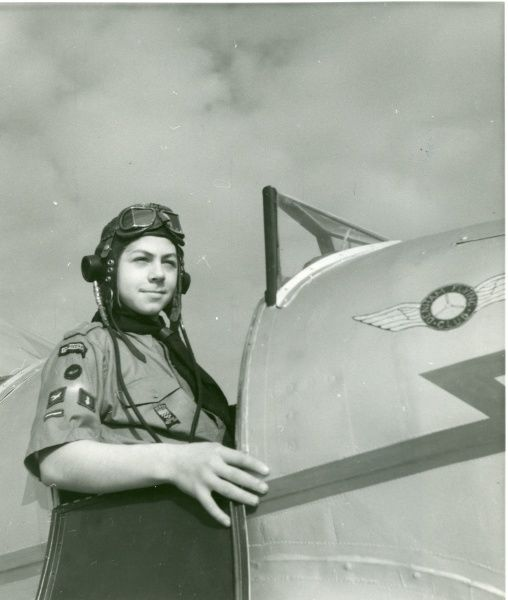 Scout wearing an aviator hat sitting in the cockpit of a Denham Flying Club Miles Magister. circa 1950s