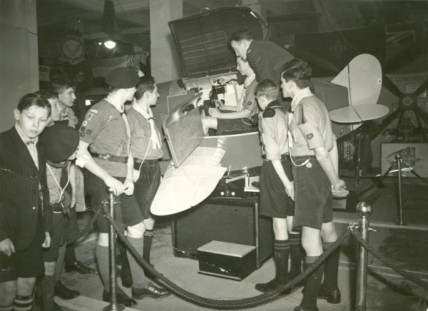 Scouts being instructed on how to operate a LINK trainer by a Royal Air Force officer. 1940s
