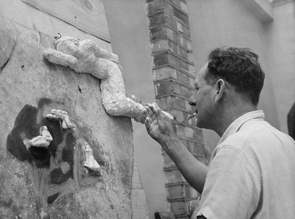 A sculptor at work on his latest contribution to art. Date: 1950s