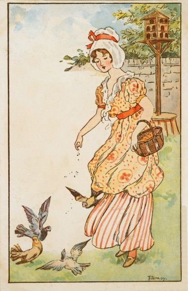 A young woman feeds birds in her garden, scattering bird seed among the birds, who have come out from their bird house