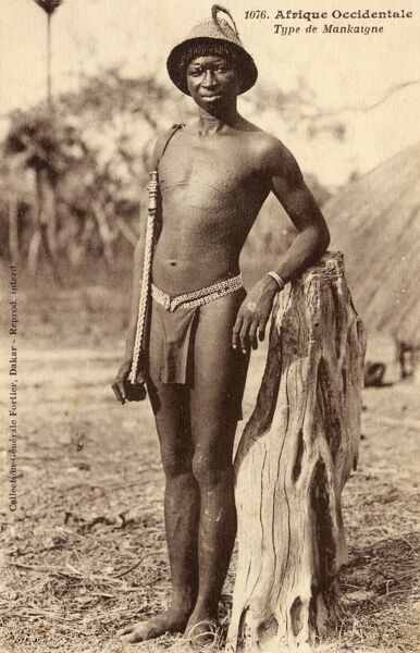 Fine photograph of a young Senegalese Man from the Makaigne tribe, displaying fine scarification across his whole upper torso, wearing a woven hat and carrying what appears to be a sling? Date: circa 1910s
