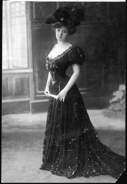 A decollete restaurant gown profusely ornamented with sequins, with short puffed sleeves, Swiss belt, floral corsage & bell shaped trained skirt. N.B hat