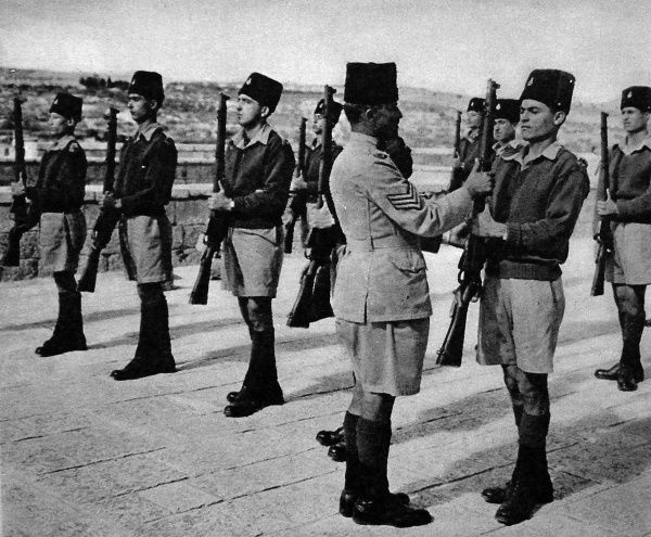 Photograph showing an Arab Drill Sergeant (centre) instructing some recent recruits to the Palestine Police Force, in Ceremonial Drill, at their barracks in Jerusalem, November 1945. Date: 1945