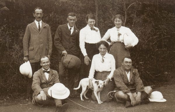 Seven people -- four men and three women -- and a dog pose for an informal photo, with pith helmets in abundance, somewhere in the Middle East