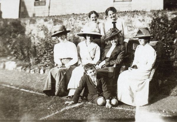 Seven people -- six women and a boy -- pose for an informal photo at the side of a grass tennis court