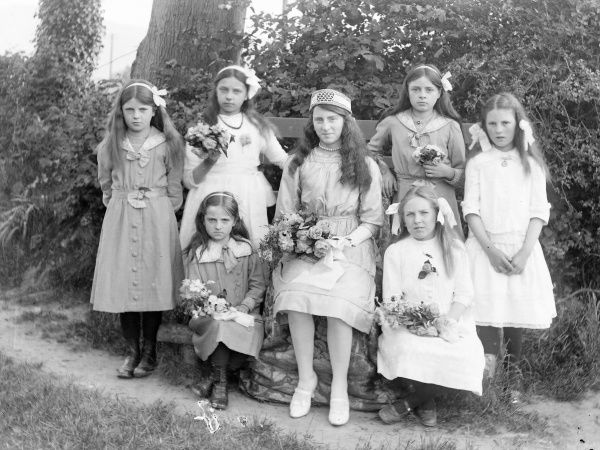 Seven sisters pose for their photograph in a garden, probably in the Mid Wales area. They are nearly all holding a bouquet of flowers