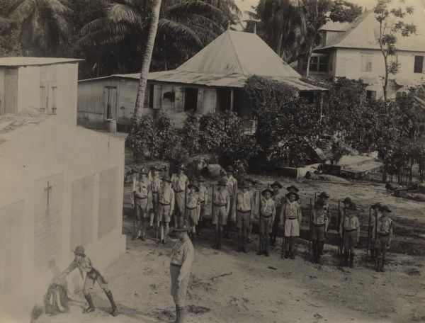Scouts on Armistice Day, laying a poppy wreath at the foot of the monument erected in Mont Fleury Cemetery in memory of the dead members of the Seychelles Labour Battalion. circa 1920s-30s