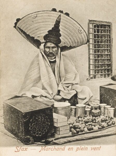 Sfax, Tunisia - Outdoor merchant in a truly spectacular hat selling traditional local tunisian cures/remedies by the side of the street
