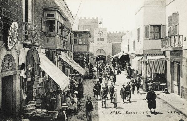 The Rue de la Republique with the British Vice Consulate at Sfax, Tunisia. The Consulate is right next door to a general store, selling pottery, overcoats and flat caps! A gentleman who is likely the Vice Consul stands at the lower left of the shot