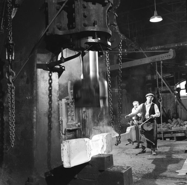 Two metalworkers use a clamp and chain to hold a large piece of metal in place while it is shaped by a pneumatic steam hammer. Possibly the early stage in the construction of a railway rail - as the initial large iron bar is stretched and shaped