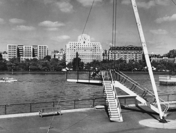 View across the Thames from the outside the Royal Festival Hall, showing the South Bank Promenade in the foreground and Shell Mex House (with clock) on the other side. Date: 1951