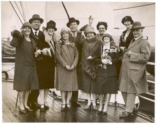 A party of cheerful travellers pose on the deck of a steamship for a souvenir photo; the third from the right carries a curious doll, perhaps a goodbye gift