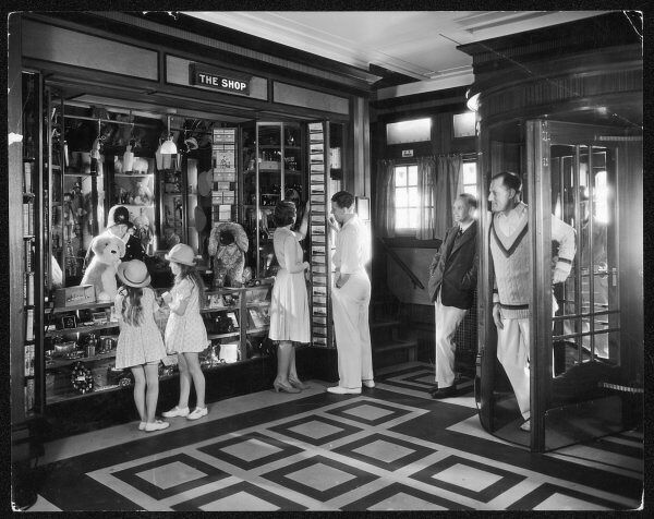 The Ship souvenir shop: Toys, gifts and radios etc. are sold. Two little girls admire a cuddly dog. A couple leaf through postcards. A cricketer and his pal are at the door